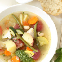 Soupe au pistou is a crowd-pleasing French vegetable soup loaded with zucchini, yellow squash and tomatoes, potatoes, beans, herbs and served with pesto