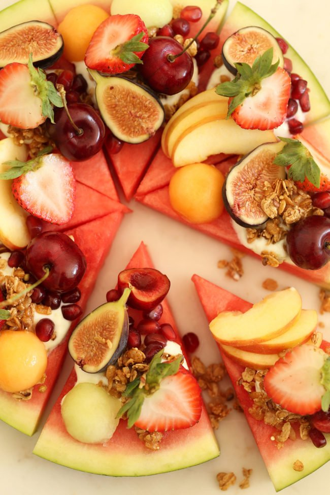 This Summery Watermelon Fruit Pizza is made of Wedges of juicy watermelon are slathered with Greek lime yogurt (sweetened only with honey), then garnished with a colorful assortment of fruit