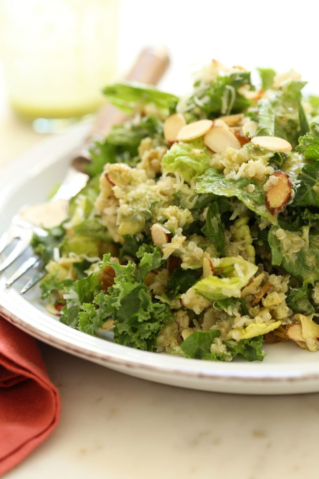 This Kale Salad with Basil Vinaigrette is loaded with curly kale, Romaine lettuce, quinoa, Parmesan cheese, toasted almonds, golden raisins, and tossed in a delicious vinaigrette