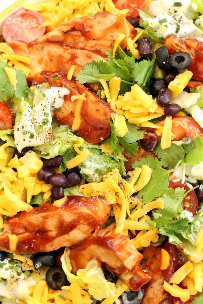 This BBQ Chicken Salad is a crowd-pleaser with tender bites of grilled chicken brushed with bbq sauce, black beans, avocado, tomatoes, fresh corn cut from the cob, cilantro,  black olives and romaine lettuce all tossed in a delicious light ranch dressing
