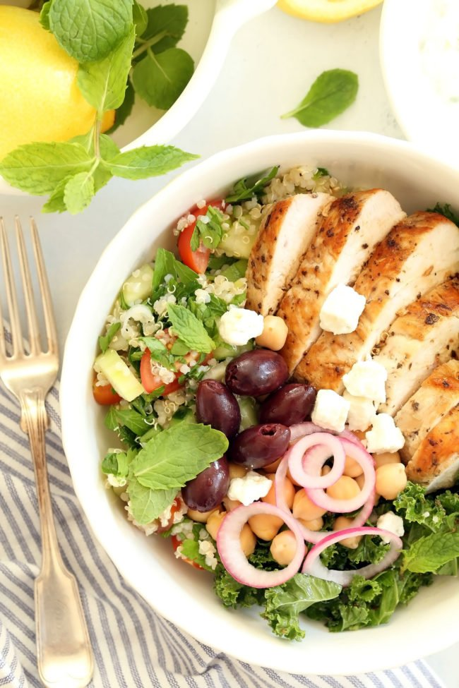 This Greek Chicken Bowl is made with marinated chicken breast, quinoa tabbouleh, kale, garbanzo beans, pickled onions, kalamata olives and feta cheese