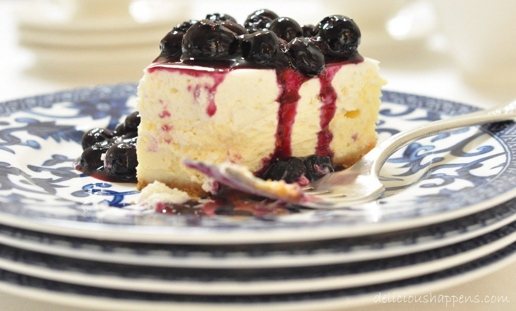 This two-layered Blueberry Cheesecake that's extra creamy with a delicate graham cracker crust and topped with a homemade blueberry sauce