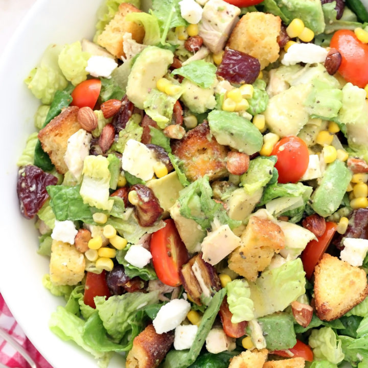This Chicken Avocado Chopped Salad  is loaded with chopped chicken,  avocado, corn,, cornbread croutons, dates, almonds, tomatoes and goat cheese