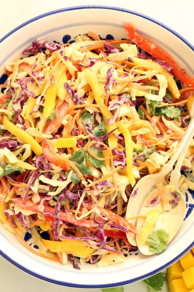 This Mango Slaw is a delicious mix of green cabbage, red cabbage, red pepper, carrots, cilantro and mango all tossed in a creamy citrus coleslaw dressing
