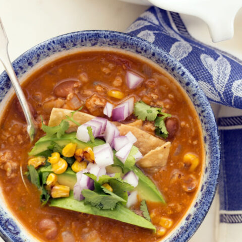 This easy taco soup combines ground turkey, refried beans, tomatoes and tortillas and simmers it all in a deliciously rich broth seasoned with classic Mexican flavors