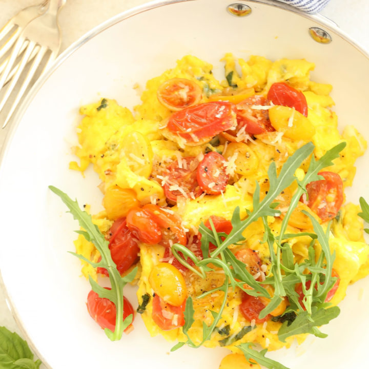 These Tomato Basil Scrambled Eggs are made with eggs, basil, cherry tomatoes and parmesan cheese