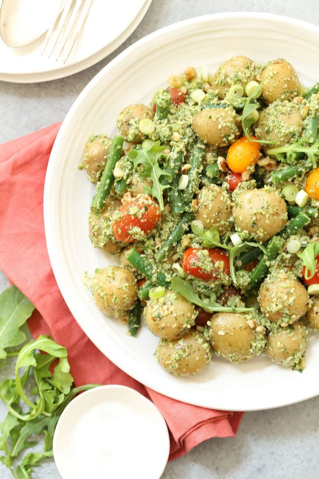 This Arugula Pesto Potato Salad is made of tender baby potatoes are mixed with green beans and heirloom cherry tomatoes, then it's all tossed in a delicious nutty arugula pesto