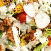 Fried Chicken Chopped Salad is loaded withfried chicken, grilled corn, green beans, radishes and cherry tomatoes all tossed in a buttermilk ranch dressing