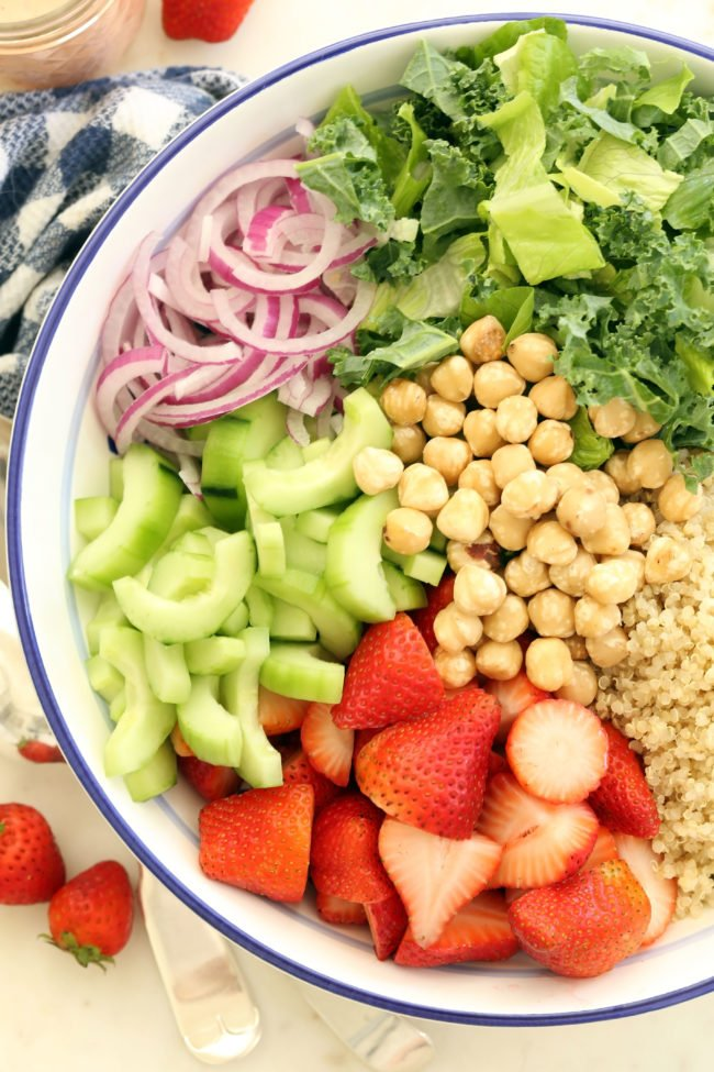 This Summer Strawberry Kale Salad is loaded with kale, quinoa, strawberries, chickpeas, onion and cucumber, and it's all tossed in a strawberry vinaigrette