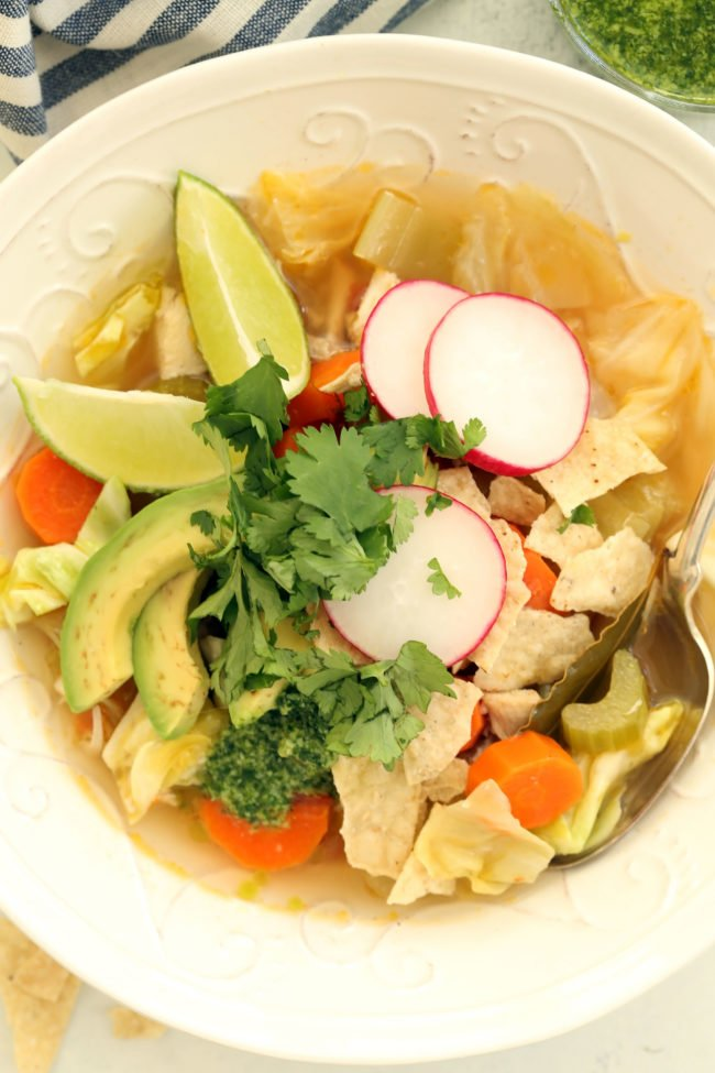 This Mexican Chicken Soup with Cilantro Jalapeno Pesto is crowded with carrots, celery and green cabbage and seasoned with classic Mexican flavors.
