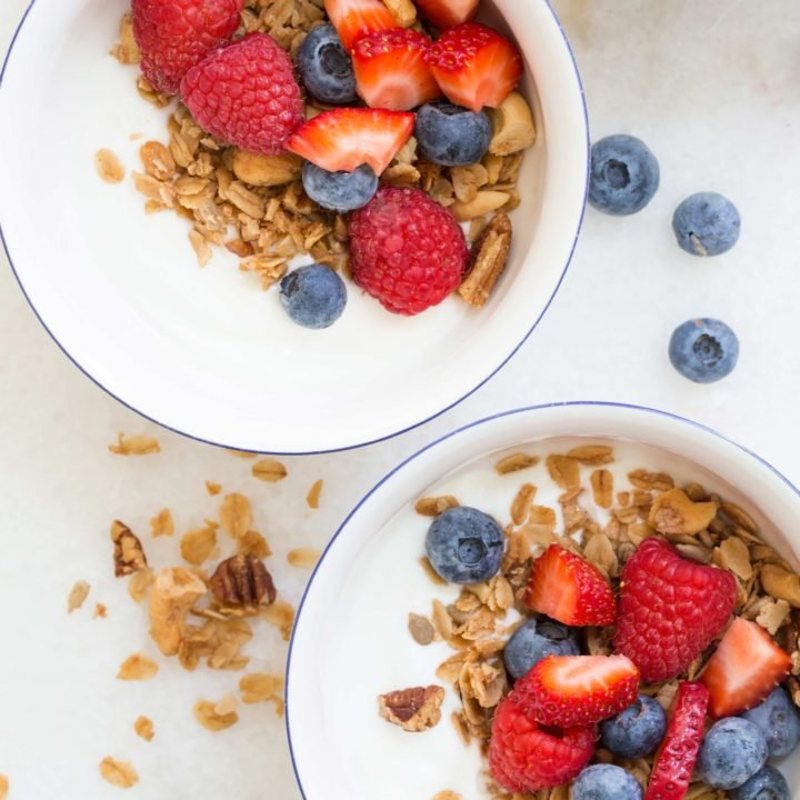 Bowls of the best granola recipe with yogurt and berries