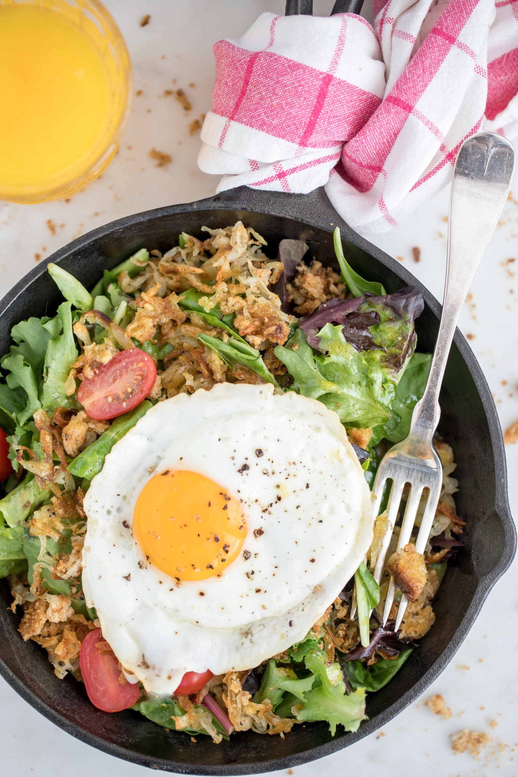 Breakfast Salad is a hearty mix of greens, hash browns, croutons, tomatoes and a fried egg, all tossed in a light citrus vinaigrette
