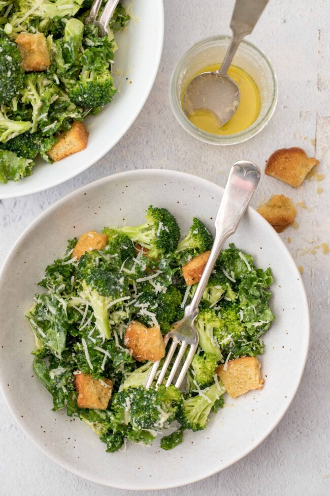 plates with broccoli and kale salad