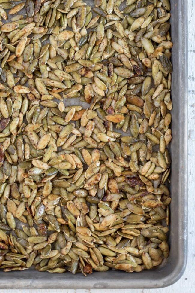 cookie sheet with raw pumpkin seeds