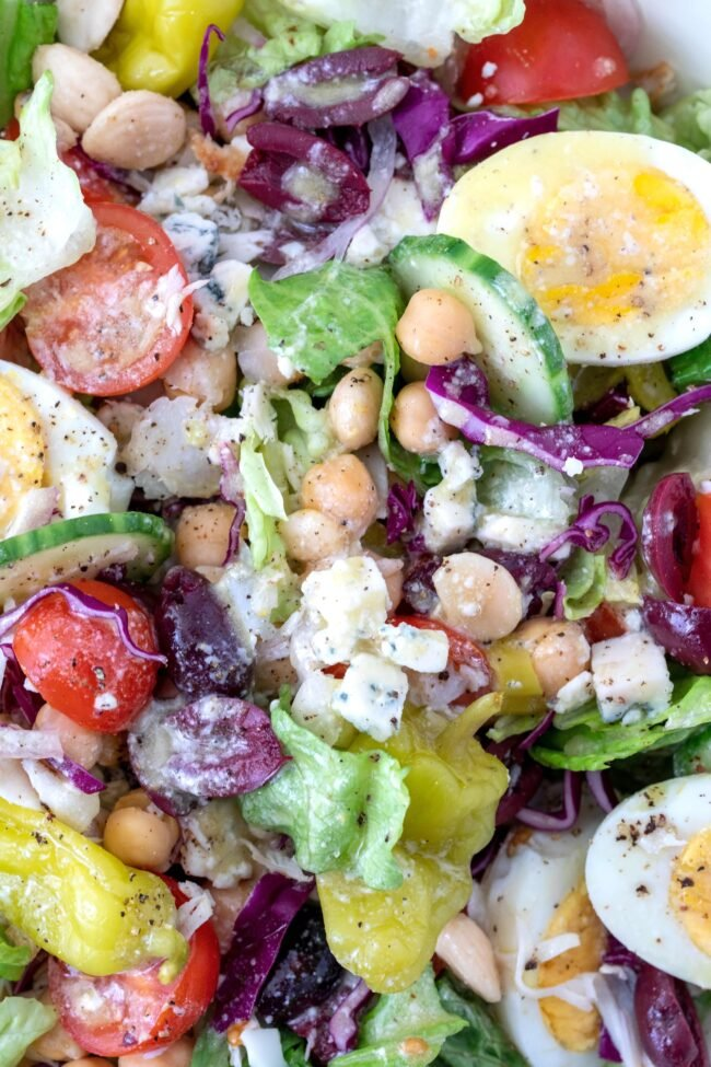 bowl of chef salad ingredients tossed in gorgonzola dressing