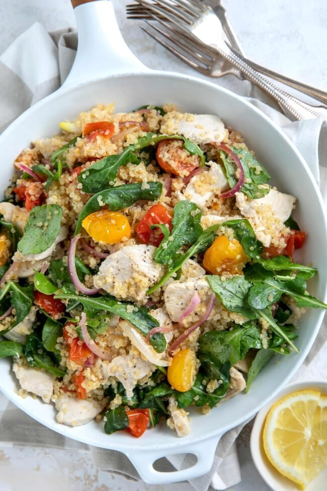 skillet with chicken and vegetables for quinoa chicken bowl