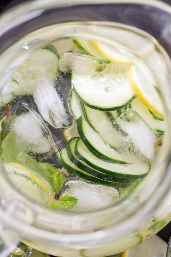 glass pitcher of water with cucumber and lemon slices for hydration