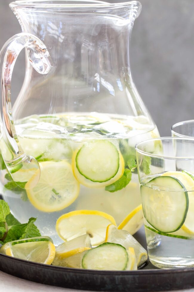 pitcher filled with water, cucumber and lemon slices