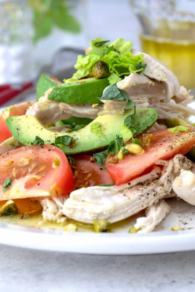 plate of avocado and tomato salad with chicken