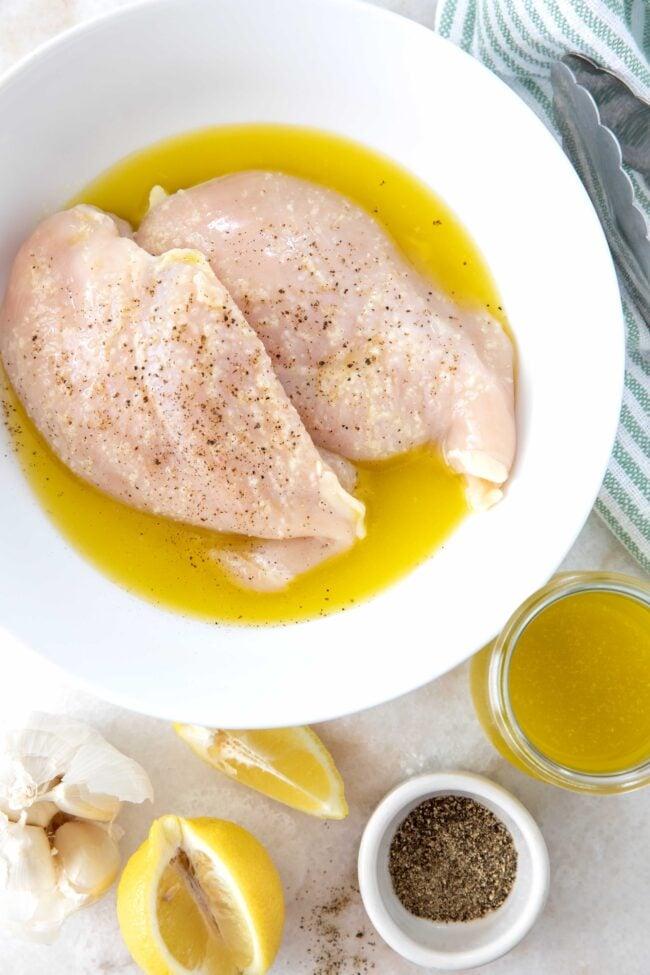 bowl of chicken breasts in lemon garlic chicken marinade